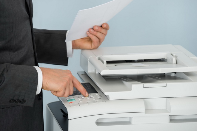 54190476 - close-up of businessman hand pressing printer's button in office