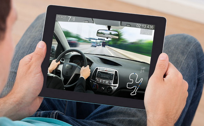 43306516 - young man playing car racing game on digital tablet at home